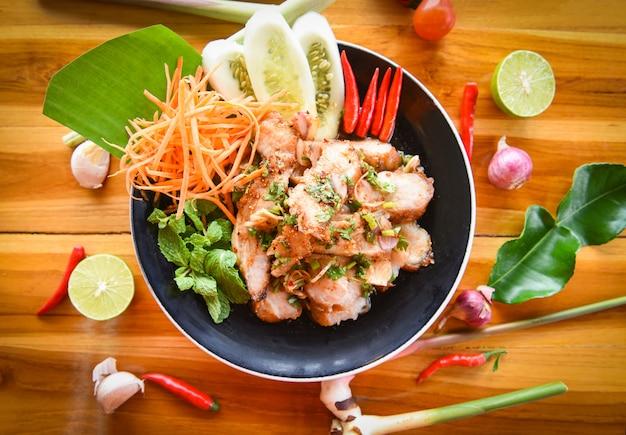 Gegrilltes thailändisches lebensmittel des schweinefleischsalats diente auf tabelle mit kräutern und gewürzbestandteilen.