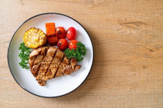 Gegrilltes und gegrilltes schweinefiletsteak mit mais, karotten und tomaten