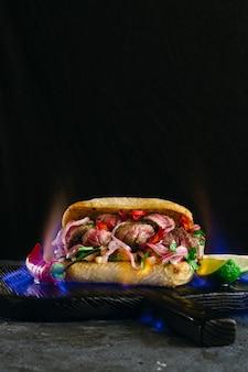 Gegrilltes würziges steaksandwichsteak in der feuerflamme auf hölzernen schneidebrettern auf dunkelheit