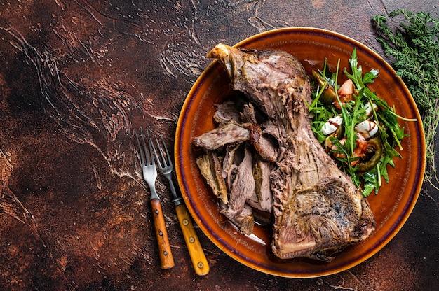 Gegrilltes ziegen- oder lamm-hammelschulterfleisch in einem rustikalen teller mit salat. dunkler hintergrund. ansicht von oben. platz kopieren.