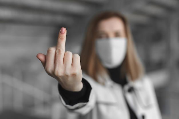 Geh weg von hier. frau mit chirurgischer medizinischer maske, die fickzeichen an der kamera zeigt. coronavirus. covid 19.