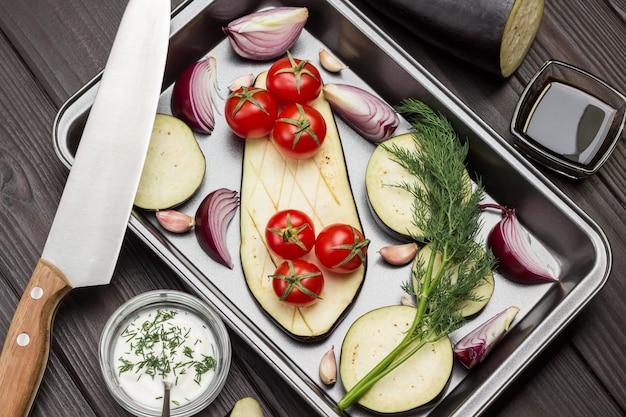 Gehackte auberginen zwiebelspalten zweig dill auf palette küchenmesser auf palette