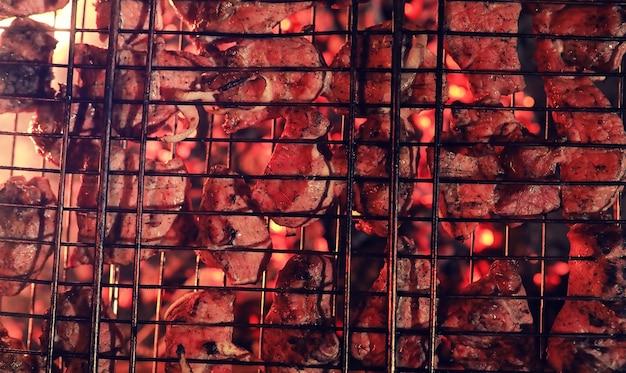 Gehackte fleischscheiben im rost zum grillen auf holzkohle im ofen. fleisch auf dem grill. schaschlik im ofen auf offenem feuer.