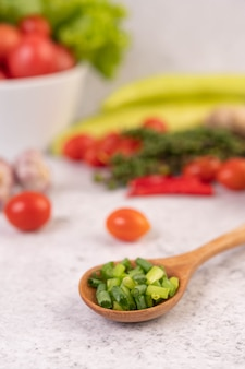 Gehackte frühlingszwiebeln auf einem holzlöffel mit paprika und tomaten auf einem weißen zementboden.