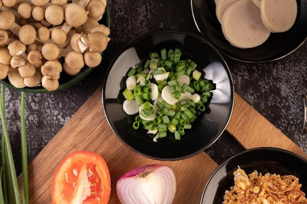Gehackte frühlingszwiebeln auf einem schwarzen teller mit chili, tomaten und knoblauch