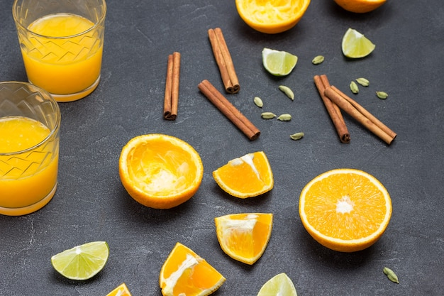 Gehackte orangen und zimtstangen auf dem tisch. zwei gläser orangensaft. schwarzer hintergrund. ansicht von oben