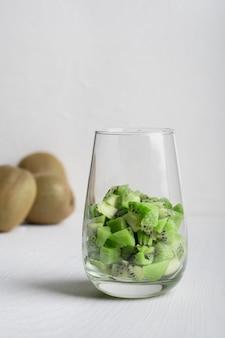 Gehackte reife grüne kiwi serviert in transparentem trinkglas auf holztisch