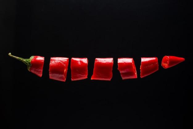 Gehackte rote chilischoten schweben in der luft. kreatives foto des fliegenden pfeffers auf schwarzem hintergrund