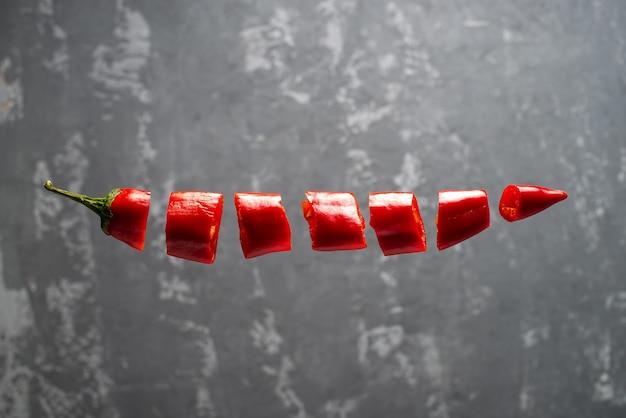 Gehackte rote chilischoten schweben in der luft. kreatives foto eines fliegenden pfeffers auf einem konkreten hintergrund