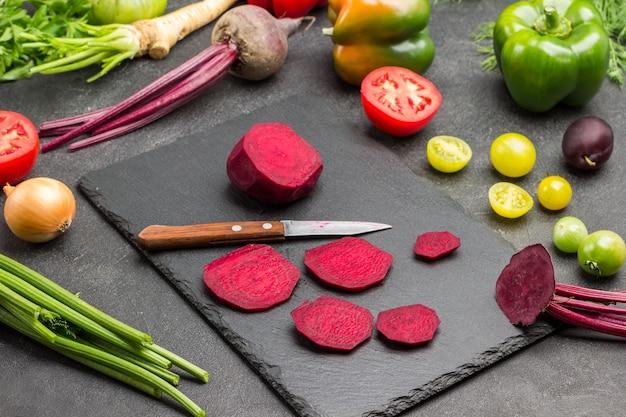 Gehackte rüben und küchenmesser auf schneidebrett. grüns und gemüse auf dem tisch. schwarzer hintergrund. ansicht von oben