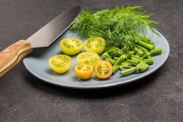 Gehackte selleriestangen, grüne tomaten und dill auf grauem teller. küchenmesser. schwarzer hintergrund. ansicht von oben