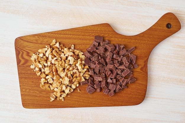 Gehackte walnüsse und schokolade auf holzbrett. schritt für schritt rezept für bananenbrot.
