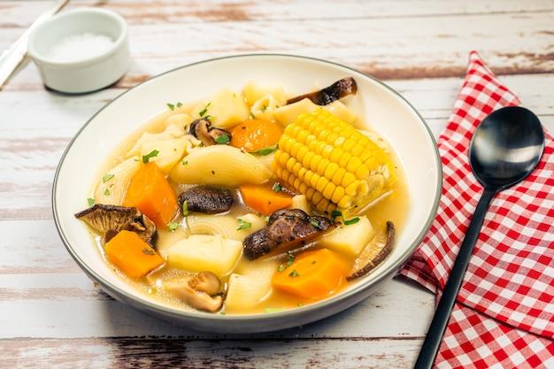 Gehackter blick auf eine exquisite hausgemachte hühner-, gemüse- und pilzsuppe mit nudeln und mais. natürliches und gesundes ernährungskonzept