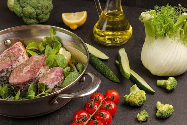 Gehackter flussfisch mit minze und rosmarin in der pfanne. brokkoli-fenchel-tomaten, gurken, glasflasche mit öl