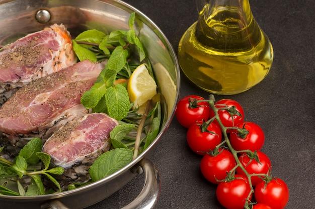 Gehackter flussfisch mit minze und rosmarin in der pfanne. tomaten, glasflasche mit öl auf dem tisch.