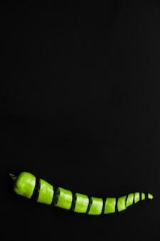 Gehackter frischer grüner paprikapfeffer auf schwarzem hintergrund