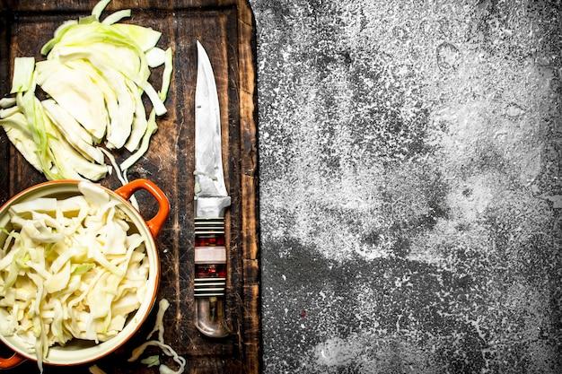 Gehackter frischer kohl auf rustikalem tisch.