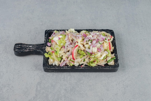 Gehackter gemüse- und obstsalat auf einem holzbrett.
