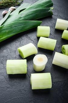 Gehackter grüner lauch oninon ungekocht mit kräuterbestandteilen, auf seitenansicht des strukturierten schwarzen hintergrunds.