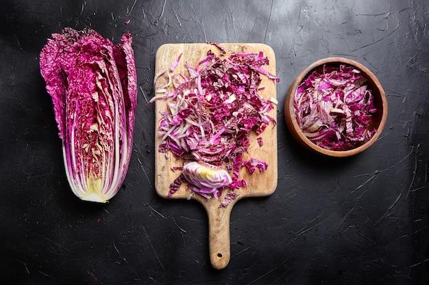 Gehackter halber rotkohl auf schwarzem tisch, draufsicht. gemüsesalat kochen, gesundes essen