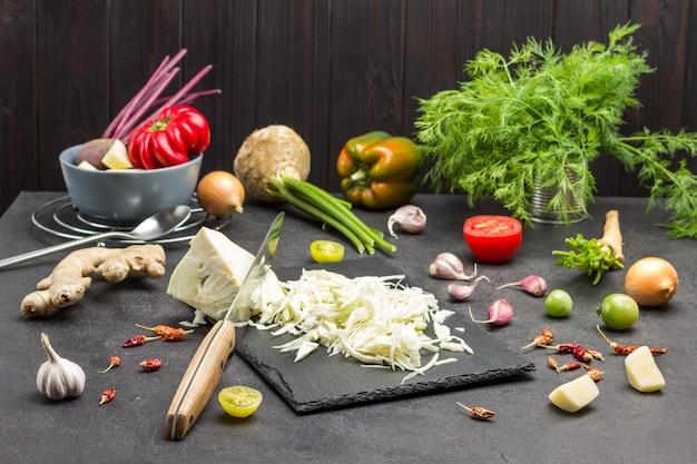 Gehackter kohl auf schneidebrett. petersilienwurzeln, sellerie, zwiebeln und grüns auf dem tisch. schwarzer hintergrund. ansicht von oben
