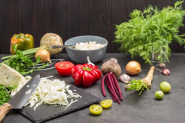 Gehackter kohl auf schneidebrett. petersilienwurzeln, sellerie, zwiebeln und grüns auf dem tisch. schwarzer hintergrund.