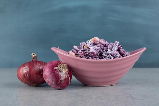Gehackter lila zwiebel-kohl-salat in keramikbechern.