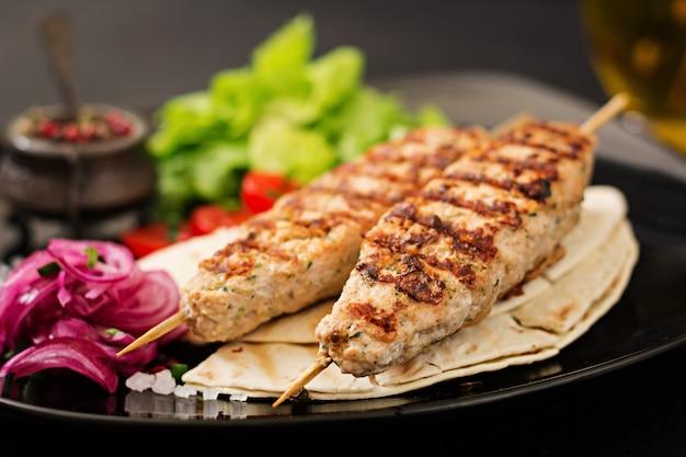 Gehackter lula kebab gegrillter truthahn (huhn) mit frischem gemüse.