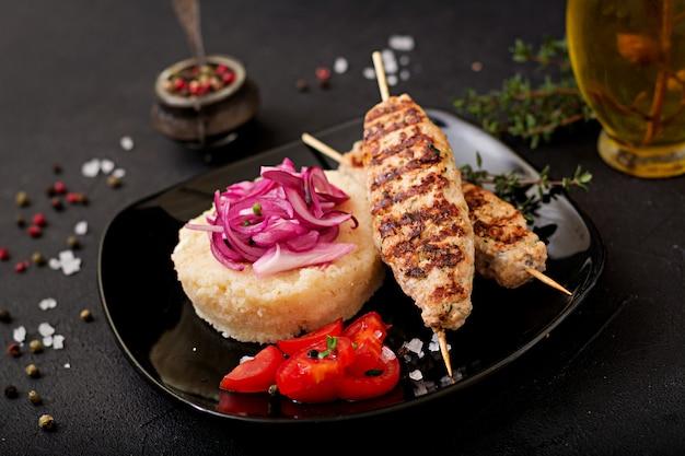 Gehackter lula kebab gegrillter truthahn (huhn) mit frischer tomate und bulgur