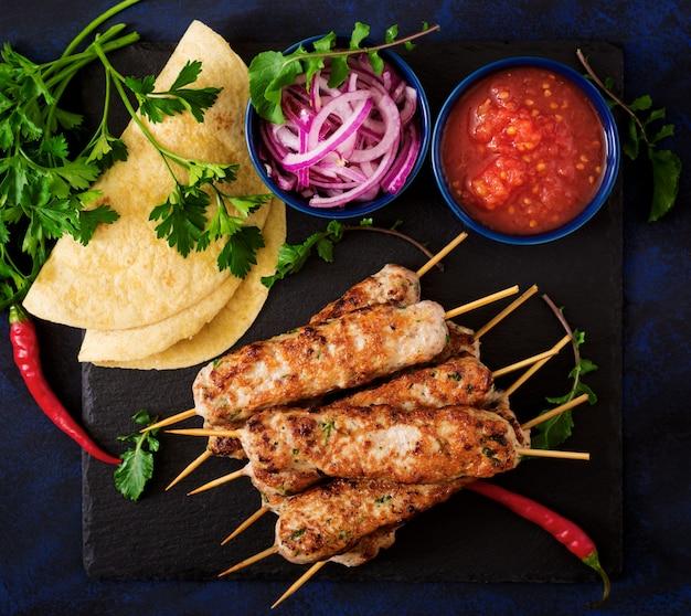 Gehackter lula-kebab gegrillter truthahn (huhn) mit gemüse. ansicht von oben