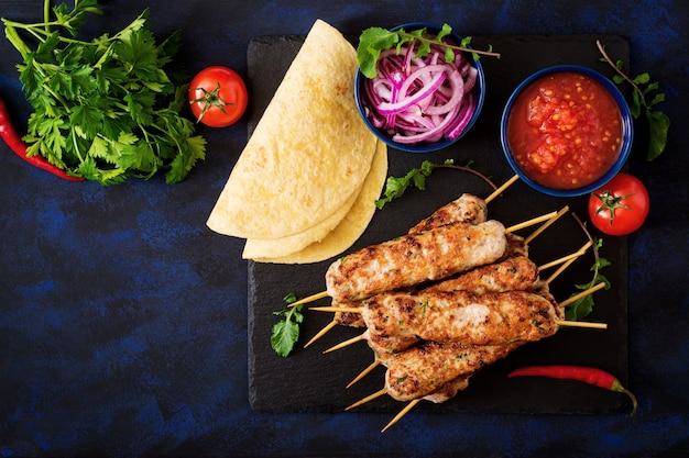 Gehackter lula kebab gegrillter truthahn (huhn) mit gemüse. draufsicht