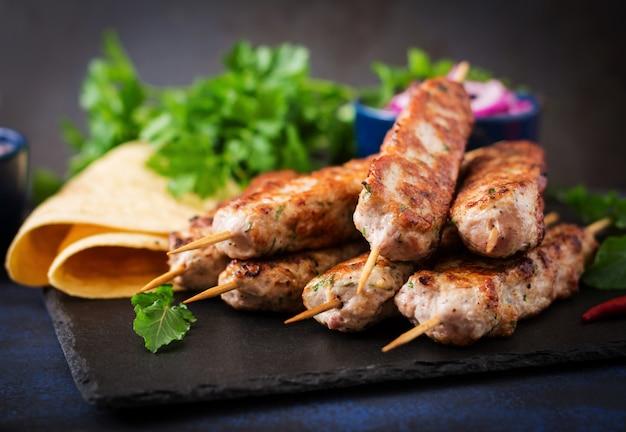 Gehackter lula-kebab gegrillter truthahn (huhn) mit gemüse.
