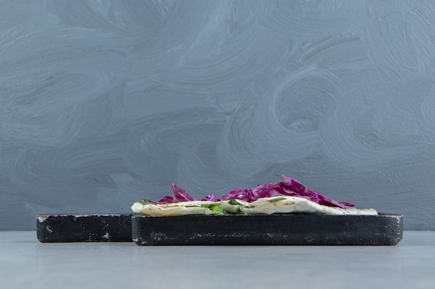 Gehackter rotkohl und gutabs auf dem tablett, auf dem marmorhintergrund.