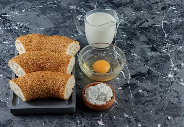 Gehackter türkischer bagelsimit mit ungekochtem hühnerei und einem glaskrug milch