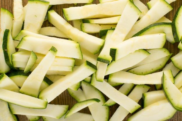 Gehackter zucchini-hintergrund. sliced squash texture draufsicht und flat lay