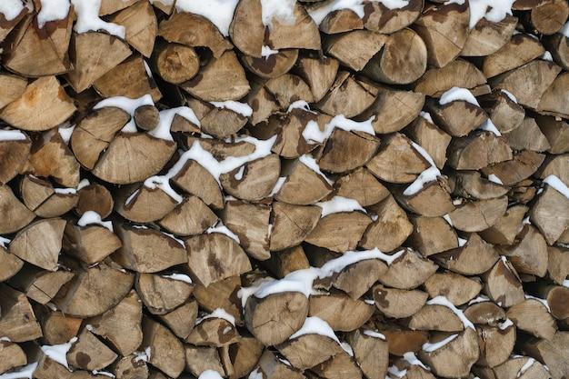 Gehacktes brennholz auf einem stapel im schnee.