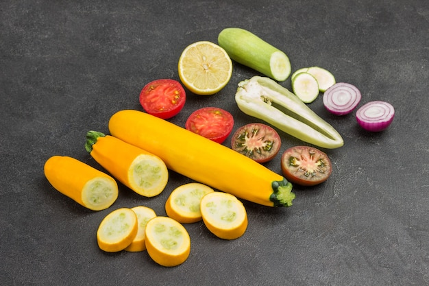 Gehacktes frisches gemüse, tomaten, paprika, zwiebeln und zucchini. platz kopieren. schwarzer hintergrund. ansicht von oben