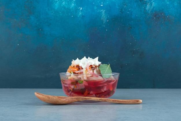 Gehacktes gemüse in glasschüssel mit löffel.