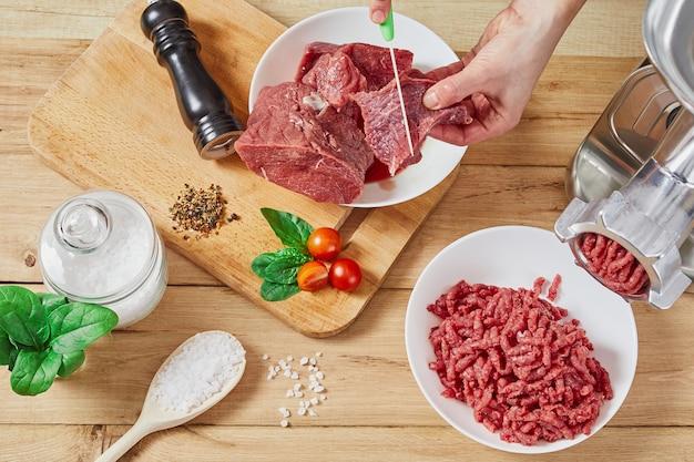 Gehacktes rohes fleisch und rinderhackfleisch. der prozess der zubereitung von hackfleisch durch einen fleischwolf.
