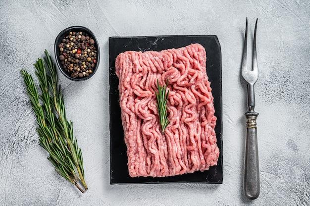 Gehacktes rohes hähnchen- oder putenfleisch auf schneidebrett mit kräutern. weißer tisch. draufsicht