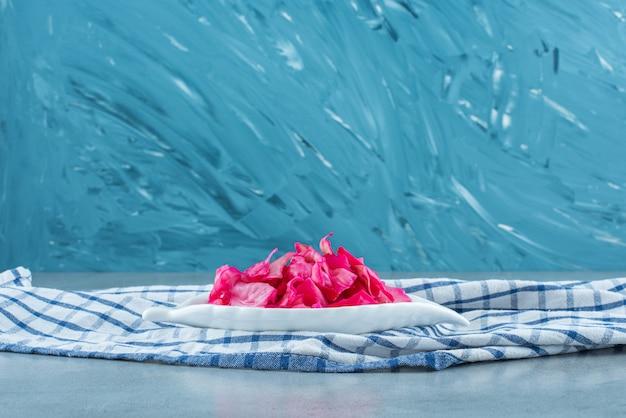 Gehacktes rot fermentiertes sauerkraut in einer schüssel auf einem untersetzer, auf dem blauen tisch.