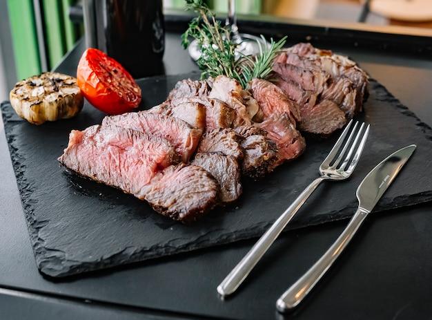 Gehacktes steak von der seite mit rosmarin und gegrillter tomate und knoblauch
