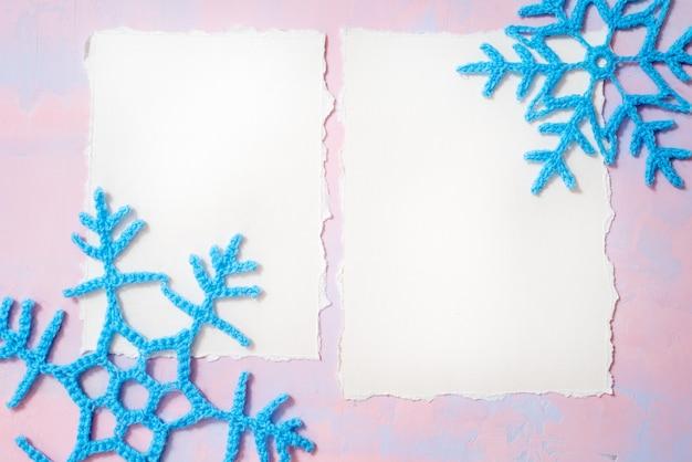 Gehäkelte schneeflocken, pink und lila. trend zerrissenes papier.stilvoll, um ihre kunstwerke anzuzeigen. nettes vintages geschenkmodell des weihnachtsneuen jahres auf rosa hintergrund. flachgelegt, draufsicht. copyspace.