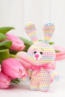 Gehäkeltes kaninchen mit zarten rosa tulpen. gestricktes spielzeug, handgemacht, handarbeit, amigurumi.