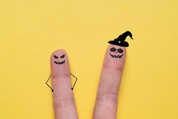 Gehässige gesichter an den fingern gemalt. halloween-urlaub.