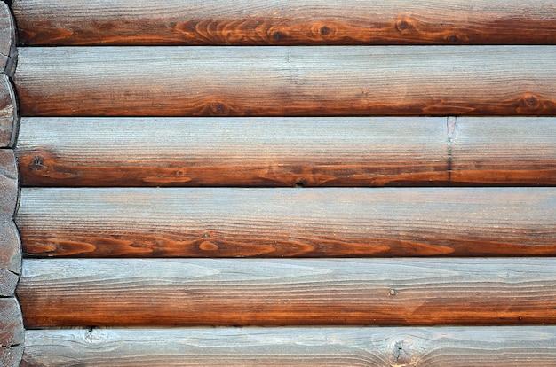 Gehauenes holz. horizontaler bauholzhintergrund der rustikalen klotzwand