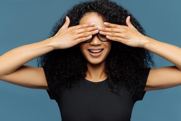 Geheime frau mit lockigem haar, bedeckt die augen, trägt eine brille, wartet auf überraschung, gekleidet in ein schwarzes lässiges t-shirt