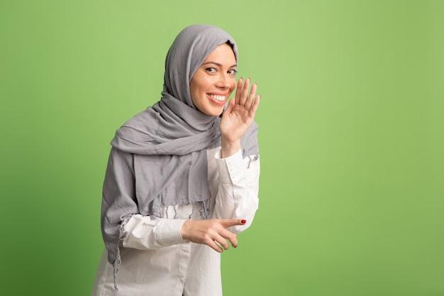 Geheimes klatschkonzept. glückliche arabische frau im hijab. porträt des lächelnden mädchens, das am grünen studiohintergrund aufwirft.
