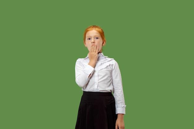 Geheimes klatschkonzept. junges mädchen flüstert ein geheimnis hinter ihrer hand. sie isolierte auf trendigem grünem studiohintergrund. junger emotionaler teenager. menschliche emotionen, gesichtsausdruckkonzept.