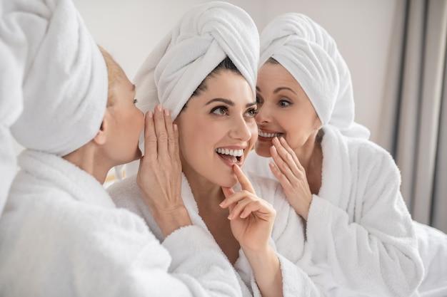 Geheimnisse der frauen. fröhliche frau mit nachdenklichem blick und zwei sprechenden freundinnen in weißen bademänteln, die zeit im spa verbringen